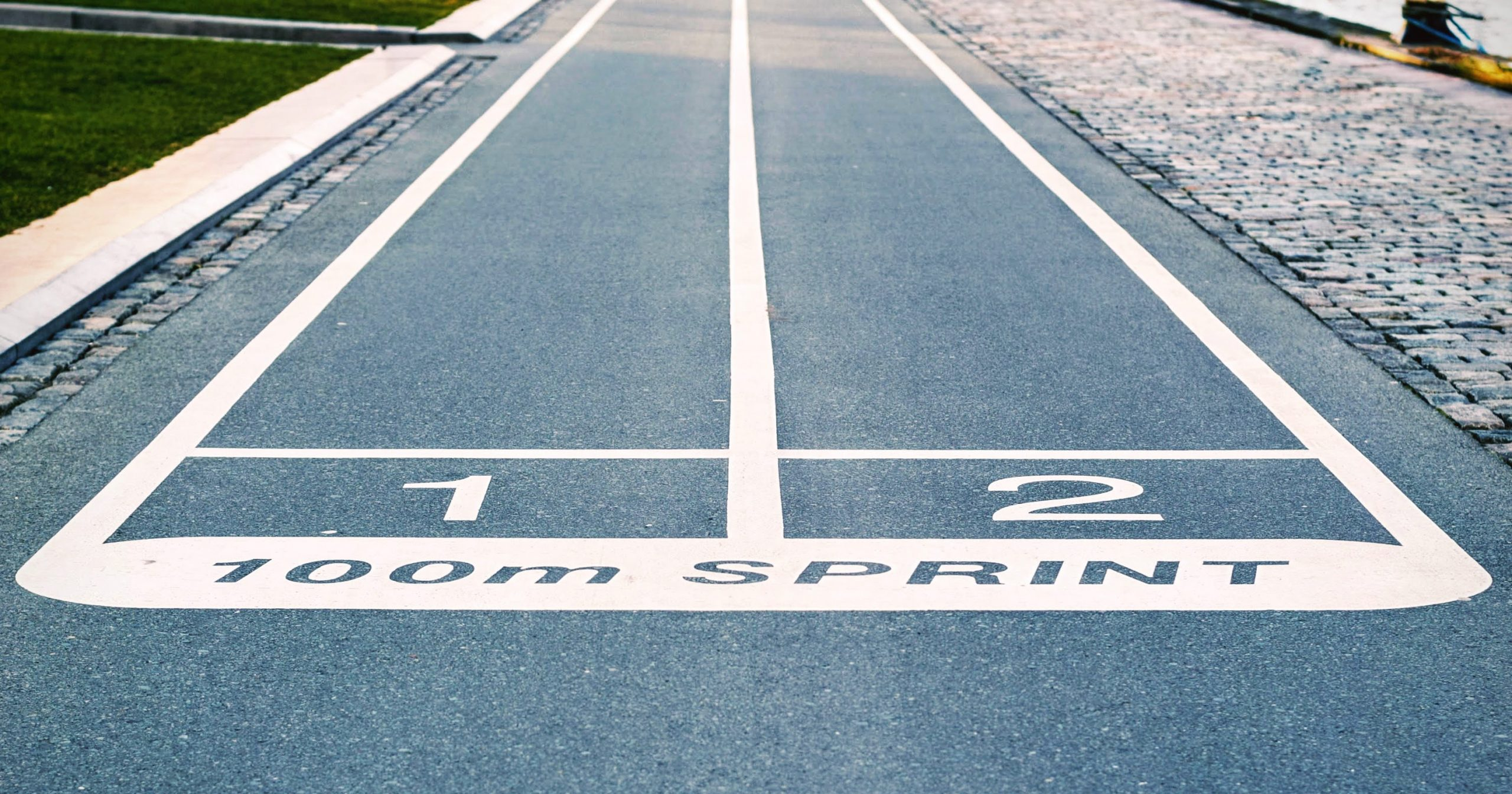 """A road with two designated lanes, labelled 1 and 2, for racing with the words """"100m Sprint"""""""